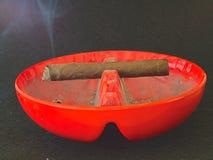 Cigarro que quema en una bandeja de ceniza sucia hrizontal Imagenes de archivo
