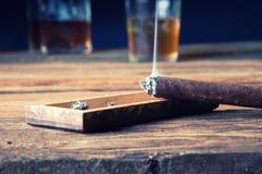 Cigarro y whisky con hielo en la tabla de madera Fotos de archivo libres de regalías