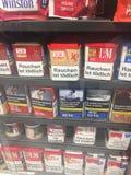 Cigarros com mensagens de advertência de empacotamento imagens de stock