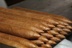 Cigarros cubanos sobre la tabla Fotos de archivo libres de regalías