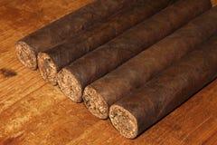 Cigarros cubanos sobre la tabla Imágenes de archivo libres de regalías