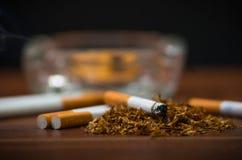 Cigarros e cigarro do close up que encontram-se dentro e em torno da bandeja de cinza de vidro na superfície de madeira, conceito Foto de Stock