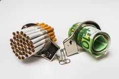 Cigarros e dinheiro com algemas - custo do fumo imagens de stock