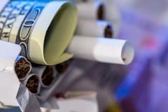 Cigarros em um bloco no dólar e no euro fotos de stock royalty free