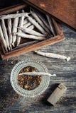 Cigarros na caixa de madeira, no cinzeiro e no isqueiro Fotografia de Stock