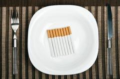 Cigarros na placa do alimento fotografia de stock