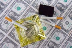 Cigarros que colocam no dinheiro Fotos de Stock Royalty Free