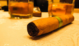 Cigarrslut och exponeringsglas av whisky på tabellen Royaltyfri Foto