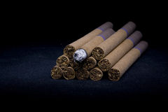 Cigars. Pyramid from the Cuban cigars with burning cigarette on the black not isolated background Stock Images