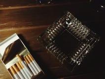 Cigars and ashtray on table. Smoking cigars and ashtray on dark brown table Royalty Free Stock Image
