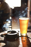 Cigratte and pint of beer. Full beer glass and cigarette with smoke rising in nightclub Stock Photo