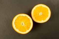 Ciie dojrzałej pomarańcze na czerń kamienia tle Fotografia Royalty Free