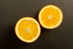 Ciie dojrzałej pomarańcze na czerń kamienia tle Obraz Stock