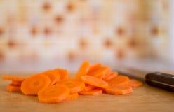 Ciie marchewki z nożem na tnącej desce w kuchni Zdjęcia Stock