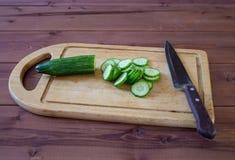 Ciie ogórek z kuchennym nożem na tnącej desce Obraz Royalty Free