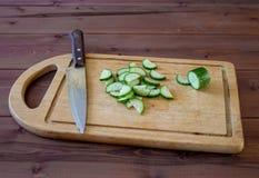 Ciie ogórek z kuchennym nożem na tnącej desce Zdjęcia Royalty Free