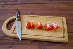 Ciie pomidory z kuchennym nożem na tnącej desce Obraz Royalty Free