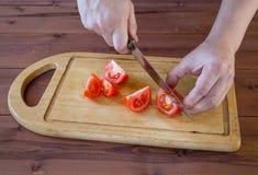 Ciie pomidory z kuchennym nożem na tnącej desce Obraz Stock