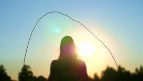 Cijfer, overzicht van een mooi, atletisch meisje met lang blond haar, touwtjespringen bij zonsondergang, tegen de blauwe hemel, i stock footage