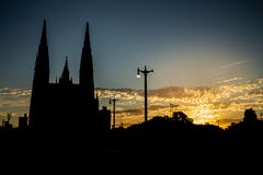 Cijfer tegen het licht van een reusachtige kathedraal Aan zijn kant de zonsondergangkleurstoffen de wolken royalty-vrije stock afbeelding