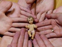 Cijfer van baby Jesus liyng op handen van een familie en een trouwring royalty-vrije stock foto