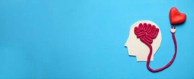Cijfer van de mens met hersenen en rood hart Liefde en intelligentie stock afbeelding