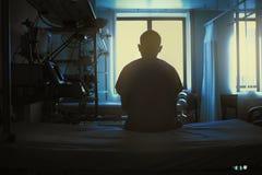 Cijfer van zittingspatiënt op een het ziekenhuisbed op de achtergrond van Royalty-vrije Stock Afbeeldingen