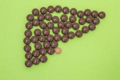 Cijfer of vormcontour van menselijke die lever, uit bruine pillen of tabletten, met gallbladder op een groene achtergrond wordt s stock afbeelding