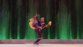Cijferschaatser die op ijs tegen kleurrijke fonteinen springen, Moskou, Rusland