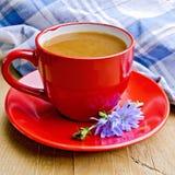Cikoriadrink i röd kopp med servetten ombord Arkivbild
