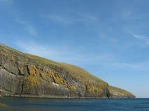 Cilan Head. The main cliff of Cilan head near Abersoch, Gwynedd, North Wales with a dark blue sea and light blue sky Stock Image