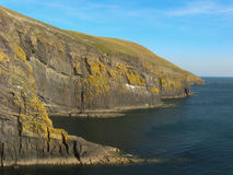 Cilan Head. The main cliff of Cilan head near Abersoch, Gwynedd, North Wales with a dark blue sea and light blue sky Stock Photography