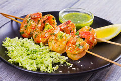 Cilantro grilled shrimps on skewers with sesame napa cabbage, green butter sauce and lemon. Skewered prawns on black plate. Cilantro grilled shrimps on skewers Stock Photo