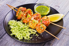 Cilantro grilled shrimps on skewers with sesame napa cabbage, green butter sauce and lemon. Skewered prawns on black plate. Stock Photos