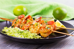 Cilantro grilled shrimps on skewers with sesame napa cabbage, green butter sauce and lemon. Skewered prawns on black plate. Cilantro grilled shrimps on skewers Royalty Free Stock Image