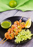 Cilantro grilled shrimps on skewers with sesame napa cabbage, green butter sauce and lemon. Skewered prawns on black plate. Cilantro grilled shrimps on skewers Stock Photography