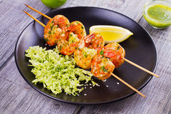 Cilantro grilled shrimps on skewers with sesame napa cabbage, green butter sauce and lemon. Skewered prawns on black plate. Cilantro grilled shrimps on skewers Royalty Free Stock Images