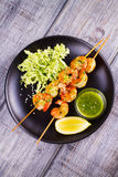 Cilantro grilled shrimps on skewers with sesame napa cabbage, green butter sauce and lemon. Skewered prawns on black plate. Royalty Free Stock Photos