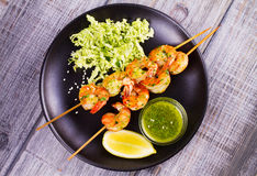 Cilantro grilled shrimps on skewers with sesame napa cabbage, green butter sauce and lemon. Skewered prawns on black plate. View from above, top studio shot Stock Images
