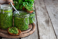 Cilantro pesto background. Homemade cilantro pesto in jars on wooden background stock images