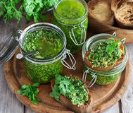 Cilantro pesto. Homemade cilantro pesto in jars on wooden background stock image