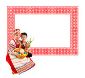 Cildren with Easter eggs and a holiday cake. Cheerful girl and boy dressed in traditional dress. She holds the basket with Easter eggs and a holiday cake. On royalty free stock images
