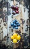 Ciliege, albicocche, uva passa in ciotole, su un fondo di legno, vista superiore fotografia stock
