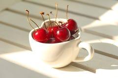 Ciliege Cile in tazza in forma di cuore su legno Fotografie Stock Libere da Diritti
