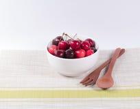 Ciliege in ciotola bianca e cucchiaio di legno su fondo bianco Immagine Stock Libera da Diritti