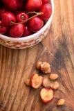 ciliege e pietre nostrane organiche in una ciotola ceramica d'annata, su fondo di legno Fotografie Stock