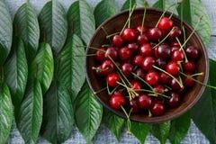 Ciliege fresche dolci con le foglie verdi su legno rustico blu Fotografie Stock
