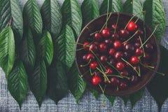 Ciliege fresche dolci con le foglie verdi su legno rustico blu Immagine Stock