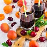 Ciliege mature organiche delle albicocche e succo fresco Fotografie Stock
