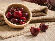 Ciliege rosse fresche sulla tabella di legno immagine stock
